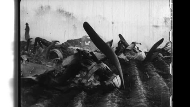 Manchurian soldiers inspect the wreckage of an American B29 bomber that was downed by a by a suicide attack