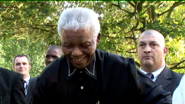 mandela along mandela waving then away helped by assistants - 90th birthday stock videos and b-roll footage