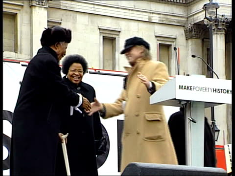 Mandela appears at antipoverty rally NGLAND London Trafalgar Square EXT SIDE LA LS Nelson Mandela along with aid of walking stick as his wife Graca...