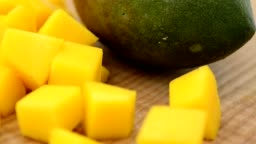 Mango pieces on a wooden board.