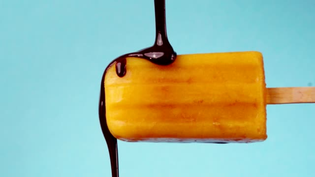 vídeos de stock e filmes b-roll de mango popsicle with dark chocolate topping - gelo