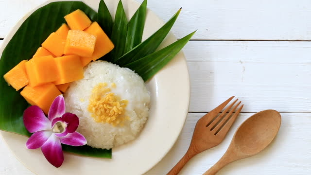 mango sticky rice in white dish of thai desserts are popular and delicious. - sticky stock videos and b-roll footage