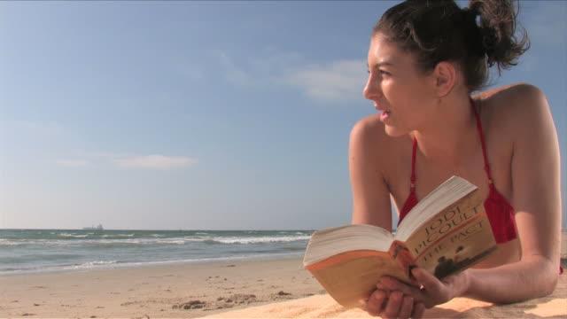 vidéos et rushes de manhattan beach, california, usaone young woman is reading a book on the beach - océan pacifique nord