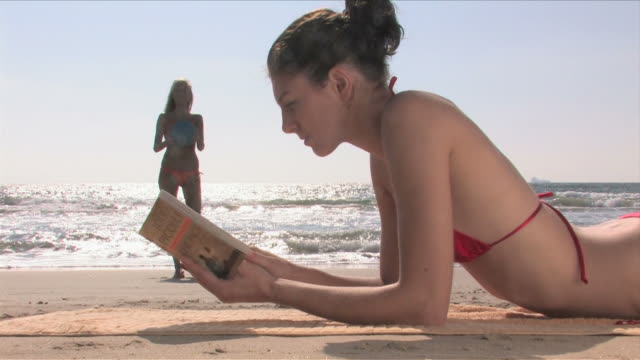 manhattan beach, california, usaone young woman is reading a book, the other woman is playing with a ball - nordpazifik stock-videos und b-roll-filmmaterial