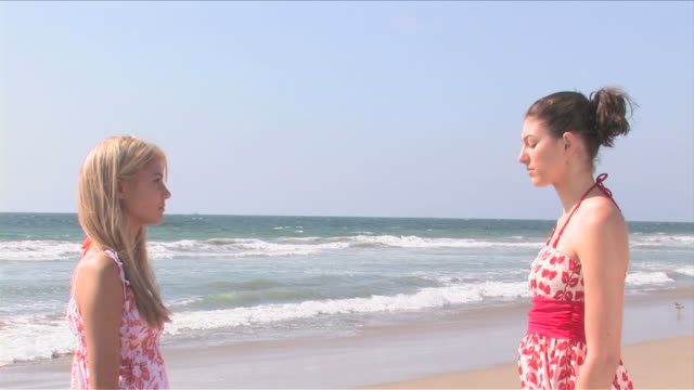 manhattan beach, california, usatwo young women are facing each other on the beach - サンドレス点の映像素材/bロール