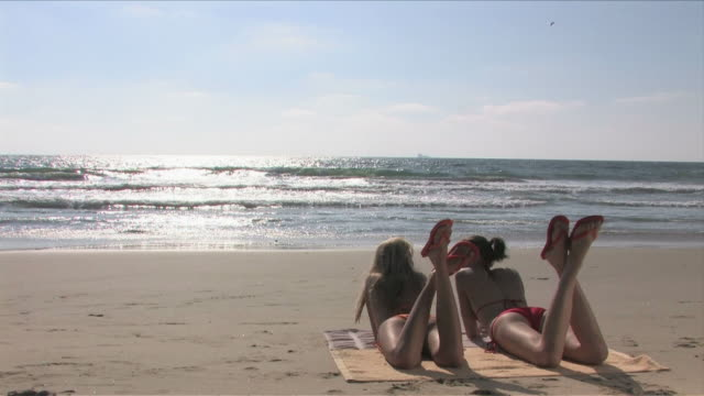 manhattan beach, california, usatwo young women are laying down on the beach - nordpazifik stock-videos und b-roll-filmmaterial
