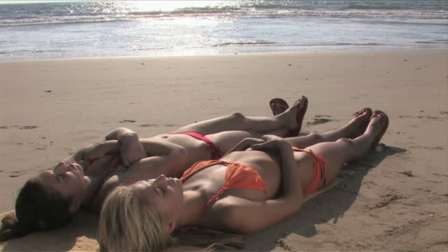 Manhattan Beach, California, USATwo young women are laying down on the beach