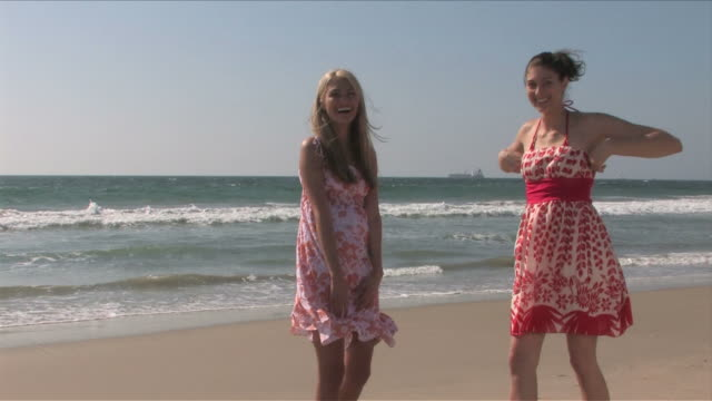 manhattan beach, california, usatwo young women are playing on the beach - サンドレス点の映像素材/bロール