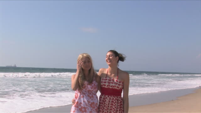 manhattan beach, california, usatwo young women are standing on the beach - サンドレス点の映像素材/bロール