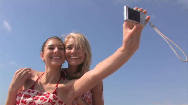 manhattan beach, california, usatwo young women are taking picture of themselves - sommerkleid stock-videos und b-roll-filmmaterial