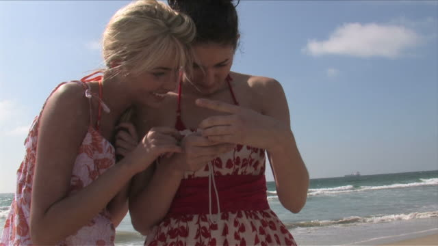manhattan beach, california, usatwo young women are taking picture of themselves - サンドレス点の映像素材/bロール