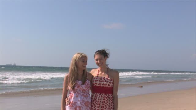 manhattan beach, california, usatwo young women are talking on the beach - サンドレス点の映像素材/bロール