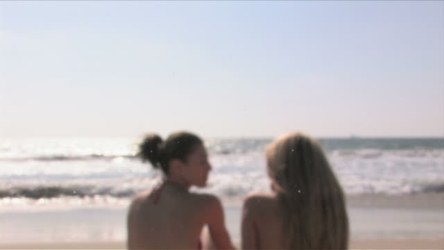manhattan beach, california, usatwo young women are talking on the beach - nordpazifik stock-videos und b-roll-filmmaterial