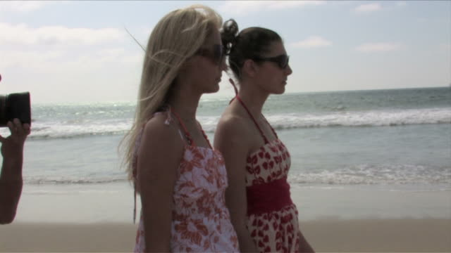 manhattan beach, california, usatwo young women are walking on the beach - サンドレス点の映像素材/bロール