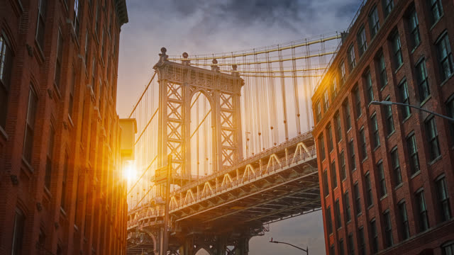 manhattan bridge and sunbeams between the buildings - ponte video stock e b–roll