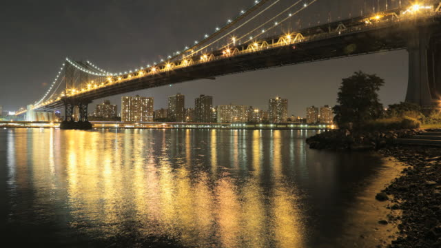 manhattan bridge at night from brooklyn with boat traffic on east river. - east river stock videos & royalty-free footage