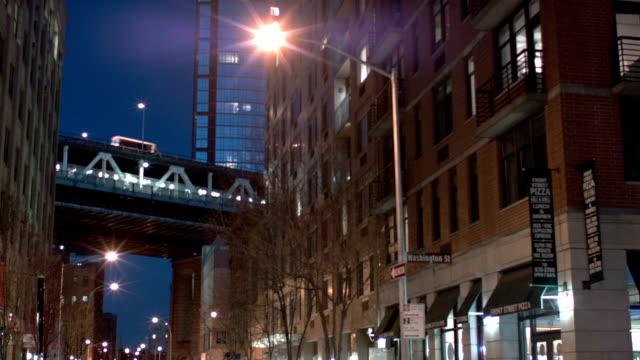 Manhattan bridge between buildings at night