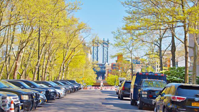 manhattan bridge in brooklyn seen between trees on the road - stationary stock videos & royalty-free footage