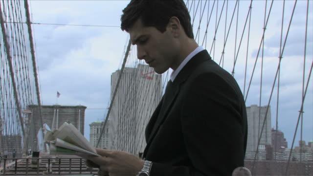 vídeos de stock, filmes e b-roll de manhattan, new york city, new york, usa, brooklyn bridgeone young business man is reading the newspaper on the brooklyn bridge - só homens jovens