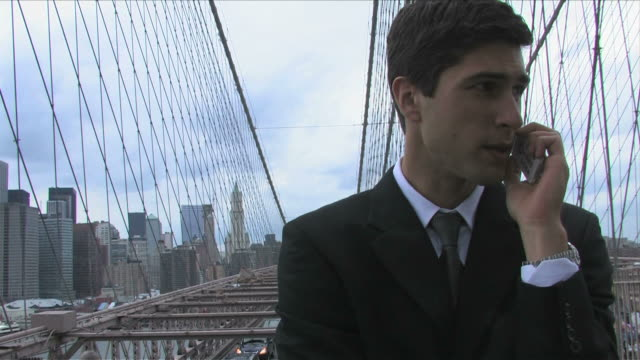 vídeos de stock e filmes b-roll de manhattan, new york city, new york, usa, brooklyn bridgeone young business man is talking on the mobile phone on the brooklyn bridge - fato completo
