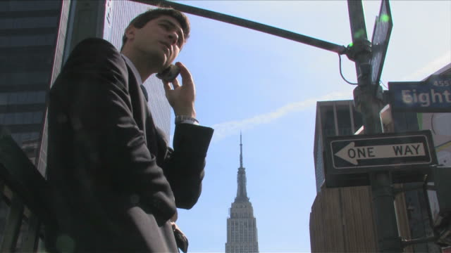 vídeos de stock e filmes b-roll de manhattan, new york city, new york, usaone young business man is talking on the mobile phone - fato completo