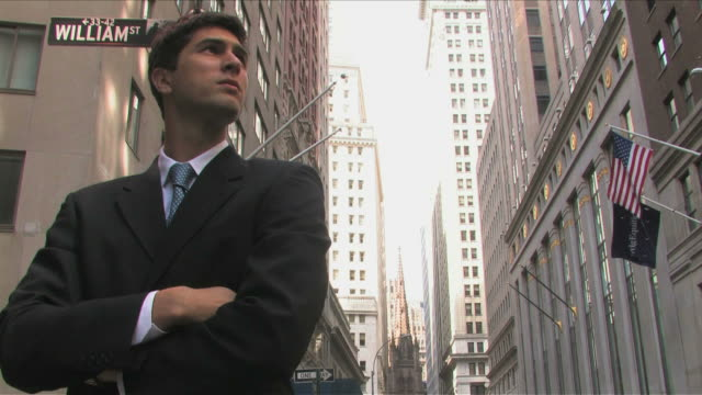 vídeos de stock, filmes e b-roll de manhattan, new york city, new york, usaone young business man is waiting for someone at wall street - placa de nome de rua