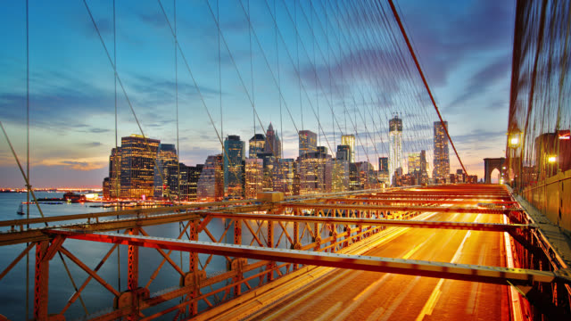 Manhattan skyline and Brooklyn bridge at night. Time lapse