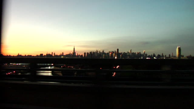 SIDE POV, Manhattan skyline seen from car crossing bridge at sunset, New York City, New York, USA