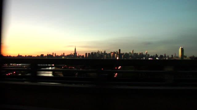 SIDE POV, Manhattan skyline seen from car crossing bridge at sunset, New York City, New York, USA