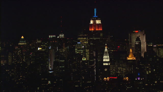 LOW AERIAL Manhattan skyline with Empire State Building illuminated at night / New York City, New York, USA