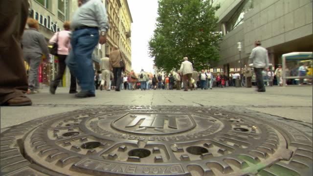 WS LA Manhole cover and pedestrians walking on Marienplatz / Munich, Bavaria, Germany