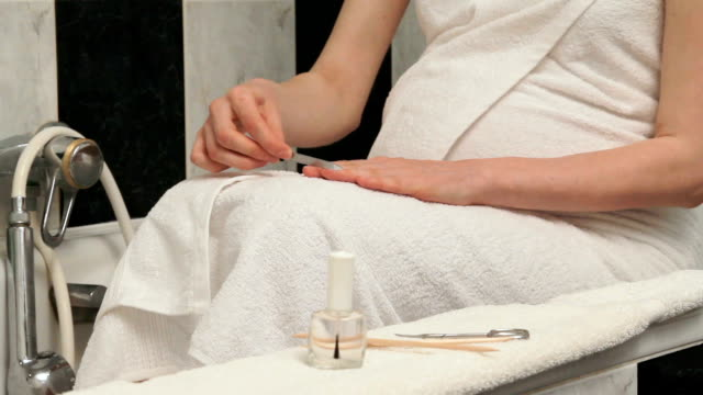 Manicure filing of female fingernail with fine nail file
