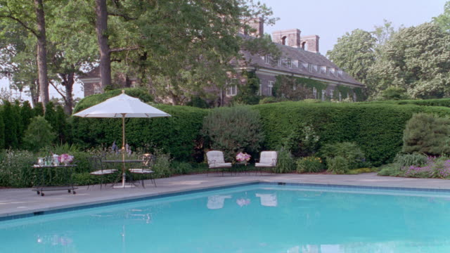 manicured landscaping and patio furniture surround an estate swimming pool. - 1995 stock videos & royalty-free footage