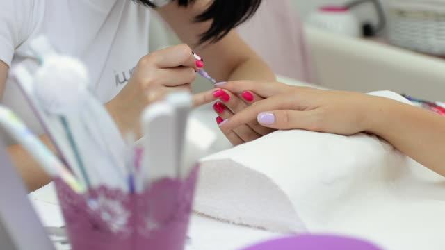 vidéos et rushes de manicuriste appliquant le vernis à ongles au salon de manucure - se faire dorloter