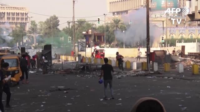 vídeos de stock, filmes e b-roll de manifestantes y fuerzas de seguridad se enfrentaron de nuevo el domingo en el centro de bagdad convertido en un campo de batalla saturado de gases... - irak