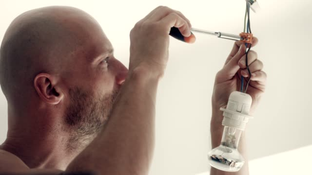 manin new home changing light bulb - changing lightbulb stock videos & royalty-free footage