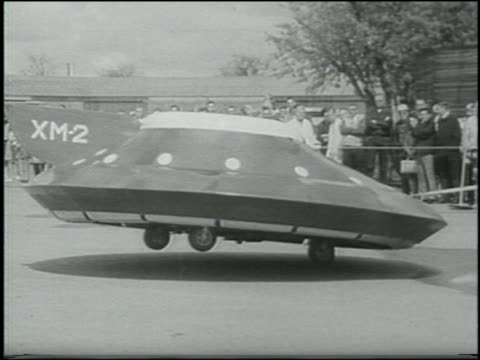 vídeos de stock, filmes e b-roll de b/w 1967 man-made hovering shakily above ground / audience in background - ufo