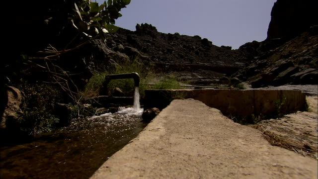 a man-made irrigation channel runs in the desert. available in hd. - irrigation equipment stock videos & royalty-free footage