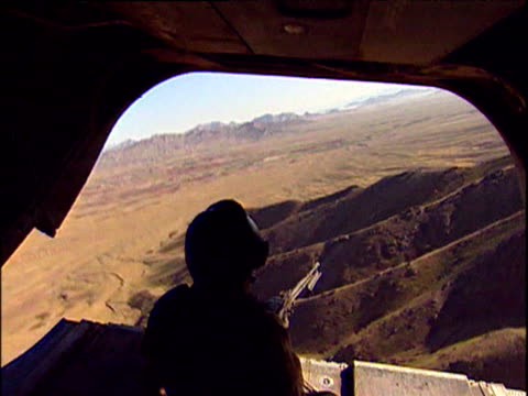 manned machine gun looking out of back of royal marines chinook helicopter flying over mountainous landscape war in afghanistan 2001 - 2001 bildbanksvideor och videomaterial från bakom kulisserna