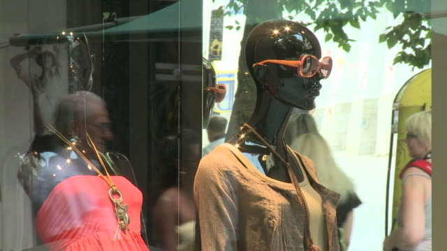 ms mannequins on display in a clothing store window with window shopping pedestrians / greece - mannequin stock videos & royalty-free footage