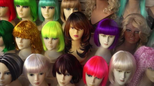 stockvideo's en b-roll-footage met mannequins wearing wigs in a wig shop store window - pruik