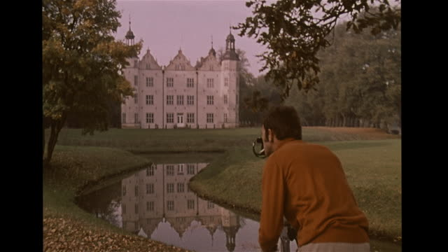 manor house reflecting in stream grassy landscape male photographer in red turtleneck smoking cigarette w/ camera on tripod fg zi ms aristocracy... - turtleneck stock videos & royalty-free footage