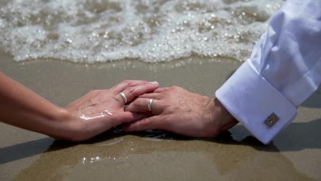 Manos boda con anillos en la playa