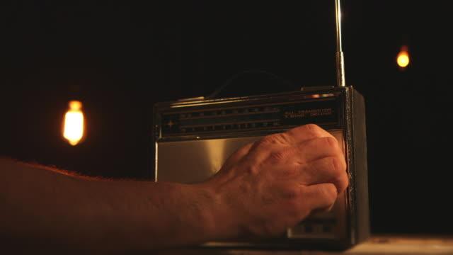 CU of man's arm adjusting old radio