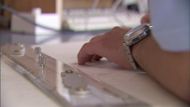 a man's arm leans across a drafting table and grabs a ruler. - 製図板点の映像素材/bロール