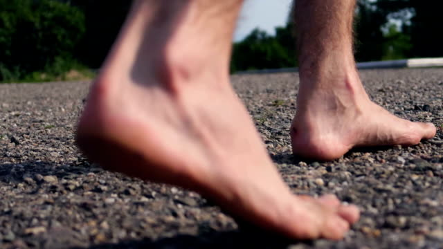 man's barefoot walking on a stone / gravel road, countryside - scalzo video stock e b–roll