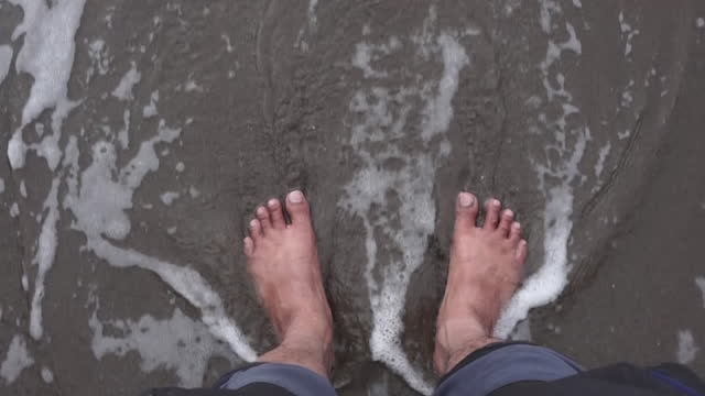 stockvideo's en b-roll-footage met a man's feet hit by the waves on the beach - benen gespreid