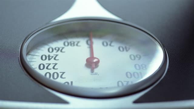 ecu, selective focus, man's feet on bathroom scale - 体重計点の映像素材/bロール