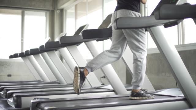 man's feet running on gym treadmill