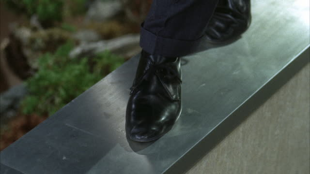 vidéos et rushes de 1966 cu ts man's feet walking along narrow ledge of building - étroit